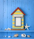 A nautical themed blank picture frame made of a beach house with shells and starfish on a blue painted background Stock Images