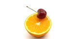 Navel orange half and fresh cherry Royalty Free Stock Image