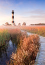 Nc bodie island lighthouse and boardwalk vertical landscape of the early in the morning as the fog still lay in the marsh the sun Royalty Free Stock Photos