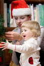 Near the christmas tree happy smiling baby girl and her mummy decorate Stock Image