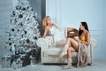 Near Christmas tree ornaments sit two girls and nice talk. Royalty Free Stock Photo