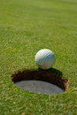 Nearly golf ball extremely close to the hole Stock Image