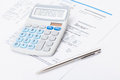 Neat calculator with silver pen and utility bill under it Royalty Free Stock Photo