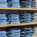 Neat stacks of folded clothing on the shop shelves Royalty Free Stock Photos