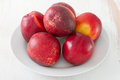 Nectarines on plate red white Stock Photos