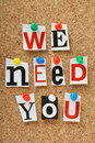 We need you the phrase in cut out magazine letters pinned to a cork notice board Stock Photo