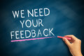 We need your feedback hand with chalk writing on blackboard business concept Royalty Free Stock Photo