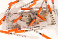Needles and dollars pile of on a hundred dollar bill signifying the rising cost of medical care or an illicit drug concept Stock Image