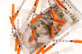 Needles and dollars pile of on a hundred dollar bill signifying the rising cost of medical care or an illicit drug concept Royalty Free Stock Photography
