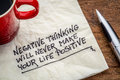 Negative thinking and posifitive life will never make your positive inspirational handwriting on a napkin with a cup of coffee Royalty Free Stock Photos
