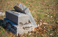 Neglected tombstone and broken in autumn leaves Stock Photo