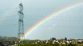 Neighborhood with rainbow coming down against huge power pole Royalty Free Stock Photo