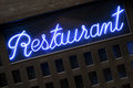 Neon blue restaurant sign lit up at night closeup Royalty Free Stock Photo