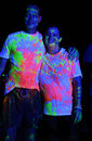 Neon colour splashed couple at glow run port elizabeth in south africa a with fluorescent pink and yellow paint the held on Royalty Free Stock Images