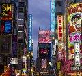 Neon lights in shinjuku district tokyo japan with various advertisments hanging a street west Stock Images