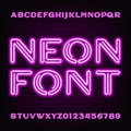 Neon tube alphabet font. Purple type letters and numbers on a dark background. Royalty Free Stock Photo
