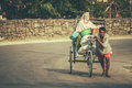 Nepali rickshaw man pulling his uphill in the town butwal Stock Image