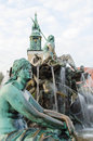 Neptunbrunnen fountaine of neptune in berlin germany detail one the sculptures the fountain with the and the saint mary s church Royalty Free Stock Images