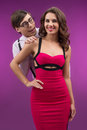 Nerd and beauty. Smiling nerd man looking over beautiful woman s Royalty Free Stock Photo