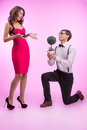Nerd and beauty young nerd man standing at his knee and holding men flower while beautiful women in red dress looking him Stock Image