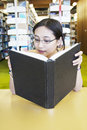 Nerd girl reading book at library Royalty Free Stock Images