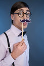 Nerd making a face young man holding stick with fake moustache at his while isolated on blue Royalty Free Stock Image