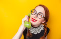 Nerd redhead girl with green phone on yellow background Stock Photos