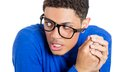 Nerdy anxious man closeup portrait of a young looking with glasses very timid shy and playing with hands nervously isolated on a Royalty Free Stock Images