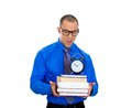 Nerdy man holding books and clock closeup of a young wearing big black glasses anxious in anticipation of finals exam test Royalty Free Stock Images