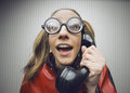 Nerdy woman speaking on a black rotary vintage phone funny nerd humor talking retro telephone wallpaper Royalty Free Stock Photo