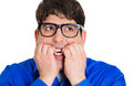Nervous anxious guy closeup portrait of nerdy young with black glasses biting his nails looking funny scared craving something Royalty Free Stock Photo