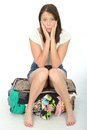 Nervous Anxious Scared Young Woman Sitting on an Overflowing Suitcase Royalty Free Stock Photo