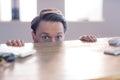 Nervous businessman peeking over desk in his office Stock Photo