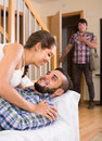 Nervous husband watching flirting spouse