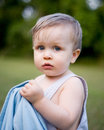 Nervous toddler boy with blanket blue eyes in overalls outside in grass holding on to blue looking Royalty Free Stock Photography