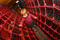 Through the net maze little girl having fun on an indoor playground in an activity centre Stock Image