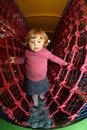 Through the net maze little girl having fun on an indoor playground in an activity centre Royalty Free Stock Images
