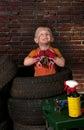 Netter und lustiger kleiner mechaniker mit einem reifen Stockbilder