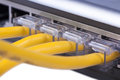 Network switch lan ports with plugged in cables four yellow close up Stock Photo