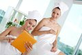 Networking in spa salon girls bath towels with touchpad Royalty Free Stock Photos