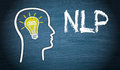 Neuro linguistic programming written on a blackboard with a human head and a light bulb Royalty Free Stock Photo