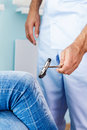 Neurologist checks reflexes hammering knee. Royalty Free Stock Photo
