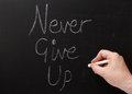 Never give up hand writing the words on a blackboard with white chalk one of the secrets or keys to success Royalty Free Stock Images