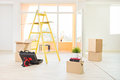 New apartment with moving boxes on the floor and a ladder focus plant and books Royalty Free Stock Photography