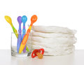 New born child stack of diapers nipple soother baby feeding spo spoons on a white background Stock Images