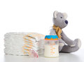 New born child stack of diapers, nipple soother, teddy bear toy Royalty Free Stock Image