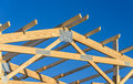A new build roof with a wooden truss framework with a blue sky background. Royalty Free Stock Photo