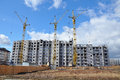 New building under construction with cranes against a blue cloudy sky and Royalty Free Stock Image