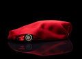 New car hidden under red cover Royalty Free Stock Image