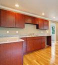 New cherry wood cabinet kitchen cabinets empty room with hardwood floor and window Stock Photo